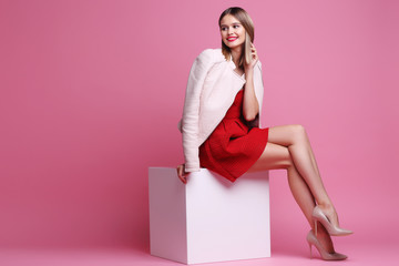 Wall Mural - Fashion portrait of young woman in pink leather jacket and red dress.