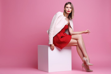 Fashion portrait of young woman in pink leather jacket and red dress. Fototapete