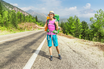 Happy Girl with hat and backpack hitchhiking on the road in Turkey, lycian way