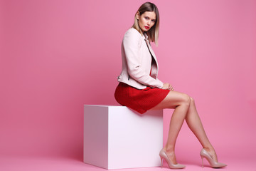 Fashion portrait of young woman in pink leather jacket and red dress. Wall mural