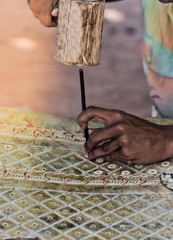 Nang Yai, Shadow Play, The hands of the craftsmen carved Leather with wooden hammer peg product, small village crafts, Siem Reap, Cambodia.