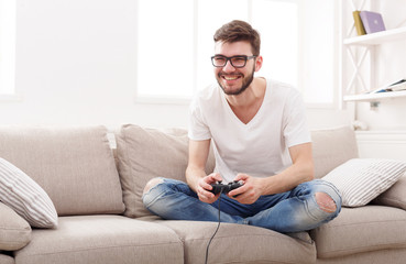 Happy young man at home playing video games