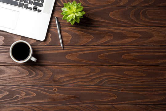 Laptop with office accessories on wooden table. Business background