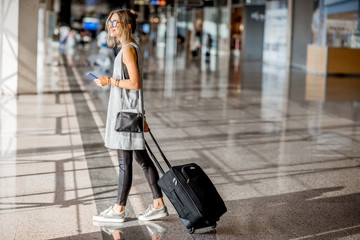 Young woman in grey dress walking with suitcase at the departure hall of the airport waiting for the flight