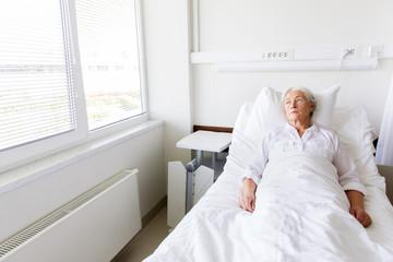 sad senior woman lying on bed at hospital ward