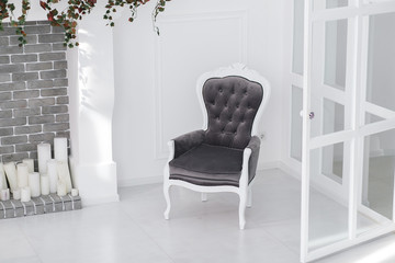 Black and white velours vintage armchair in minimalistic scandinavian room with brick fireplace and candles. horizontal photo with clear space for text