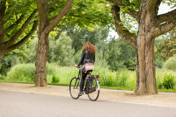 Girl biking on a omabike in the Amsterdam Vondelpark