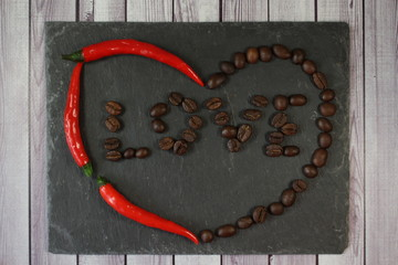 Heart love chili coffee. Abstraction of heart shape of red hot chili pepper and brown coffee beans on the background of natural black stone. With the inscription love in the heart center.
