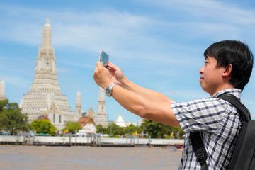 Tourists holding a mobile phone to take pictures yourself smiling with Wat Arun at Thailand.