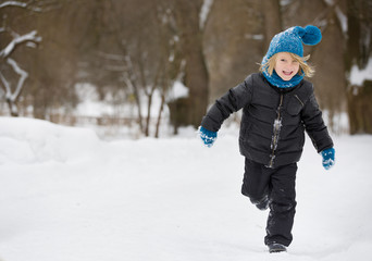 Portrait of adorable little kid boy with long blond hair running and playing with snow outdoors in the park. Child with blue scarf and hat walking and having fun on a windy winter day.