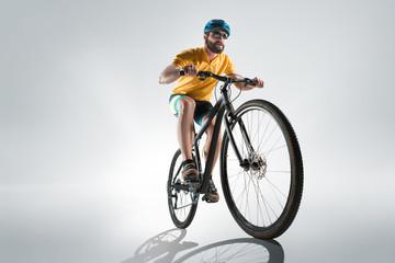 The bicyclist on gray, studio shot. Wall mural