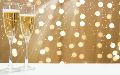 Two glasses of foaming champagne on the background of festive garlands, copy space for your text on the right