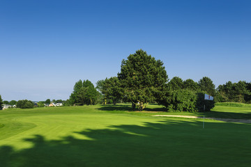 General view of a green golf course on a bright sunny day. Idyllic summer landscape. Sport, relax, recreation and leisure concept