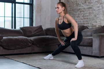 Attractive young woman training indoors doing side lunges working out legs, hips and buttocks