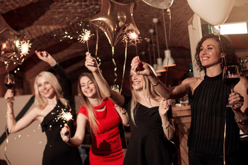 Group of happy smiling girlfriends wearing evening dresses celebrating New Year holding sparklers in decorated cafe