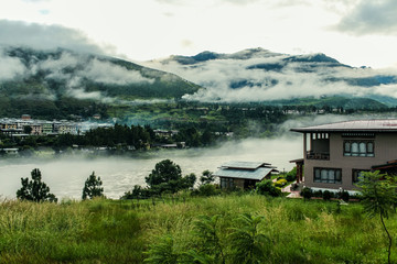 Bhutanese village near the river on a foggy day at Punakha, Bhutan