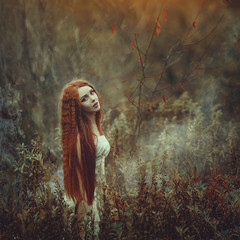 A beautiful young woman with very long red hair as a witch walks through the autumn forest.