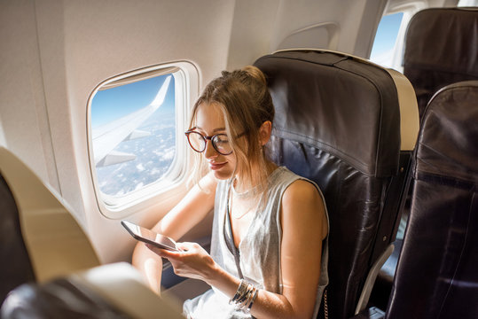 Young woman sitting with phone on the aircraft seat near the window during the flight in the airplane