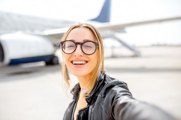 Young happy woman making selfie photo in front of the airplane on the airport runway before the departure