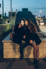 two young women outdoor city night using smart phone - internet, social network, technology concept