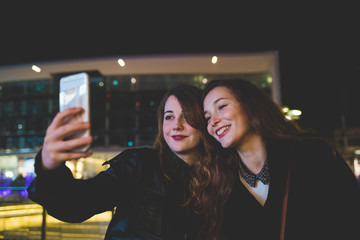 two young women outdoor city night using smart phone taking selfie - internet, social network, technology concept