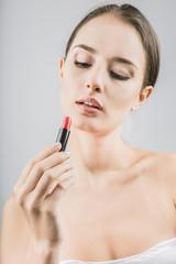 beautiful girl holds lipstick