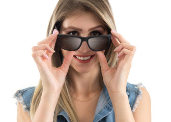 Friendly woman looks over the sunglasses. Blonde person wearing jeans vest. White background..