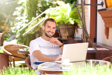 Handsome man with laptop resting in street cafe