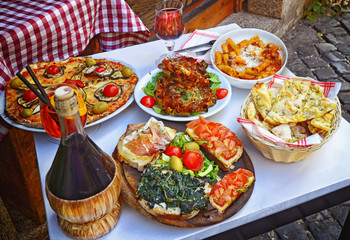 A summer  dinner .Pasta , pizza  and homemade food arrangement  in a restaurant  Rome   .Tasty and authentic Italian food.