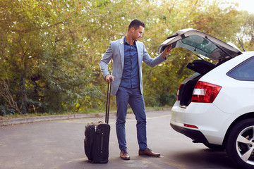 Young business man closes car trunk