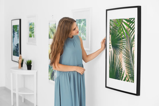 Young woman looking at picture of tropical foliage in art gallery