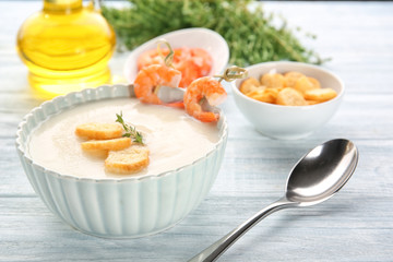 Tasty cream soup with shrimps in bowl on table