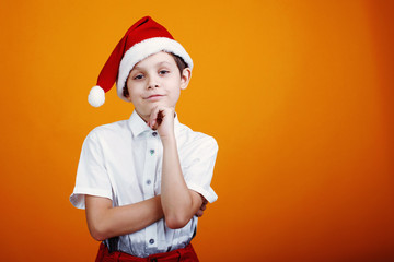 Cute little boy in a cap Santa Claus on a yellow background. Copyspace