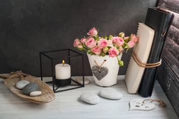 Pink roses in concrete pot with candle