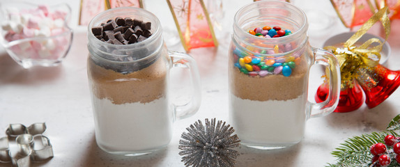 Christmas homemade gift concept, ingredients for preparation chocolate and rainbow cookies in jar, marshmallow in dish, metallic cutting forms for cookies and decorations on kitchen table