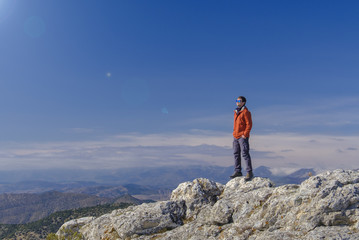 Man standing at the peak of rock mountain. Daylight