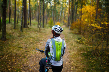 Image from back of sports woman in helmet on bicycle