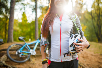 Photo of young sporty woman with helmet on background of bicycle at autumn forest