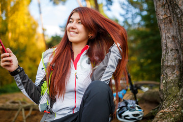 Picture of happy woman with smartphone in autumn forest