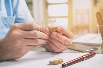 Doctor holding hearing aid