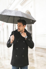 Handsome man with umbrella in the rain