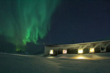 Aurora Borealis over fiord in the Arctic.