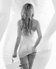 the bottom of a girl in a white top with long blonde hair and a ribbon in the hand