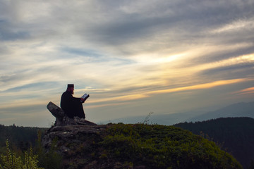 priest reading in the sunset light, Romania