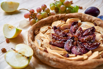 A homemade apple plums pie on light wooden table decorated with fresh apples, plums, grapes, brown raisins and sesame on blurred background. Side view