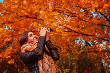Young photographer takes pictures of autumn forest