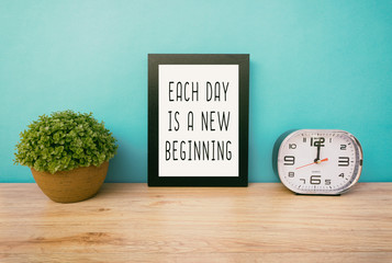 Motivational and inspirational life quotes - Each day is a new beginning. Frame and plant with teal blue background, retro style.