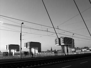 Blick über die Gleise der Straßenbahn auf der Severinsbrücke auf den Rheinauhafen mit den Kranhäusern in Köln am Rhein, aufgenommen in Schwarzweiß