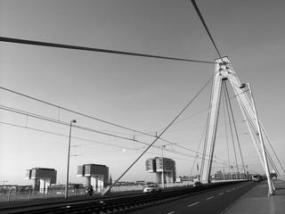 Brückenpfeiler und Spannseile der Serverinsbrücke über den Rhein in Köln, fotografiert in neorealistischem Schwarzweiss