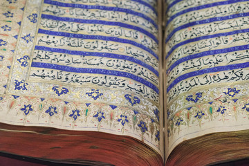 Reading the ancient Holy Quran. The open book at the Islamic Arts Museum in Kuala Lumpur, Malaysia